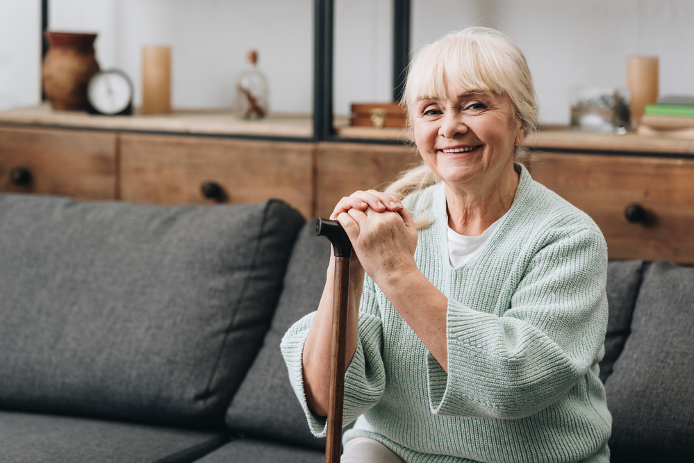 Elderly woman on sofa holding cane