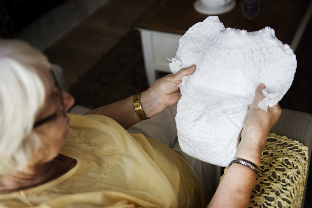Senior woman holding and looking at adult diaper