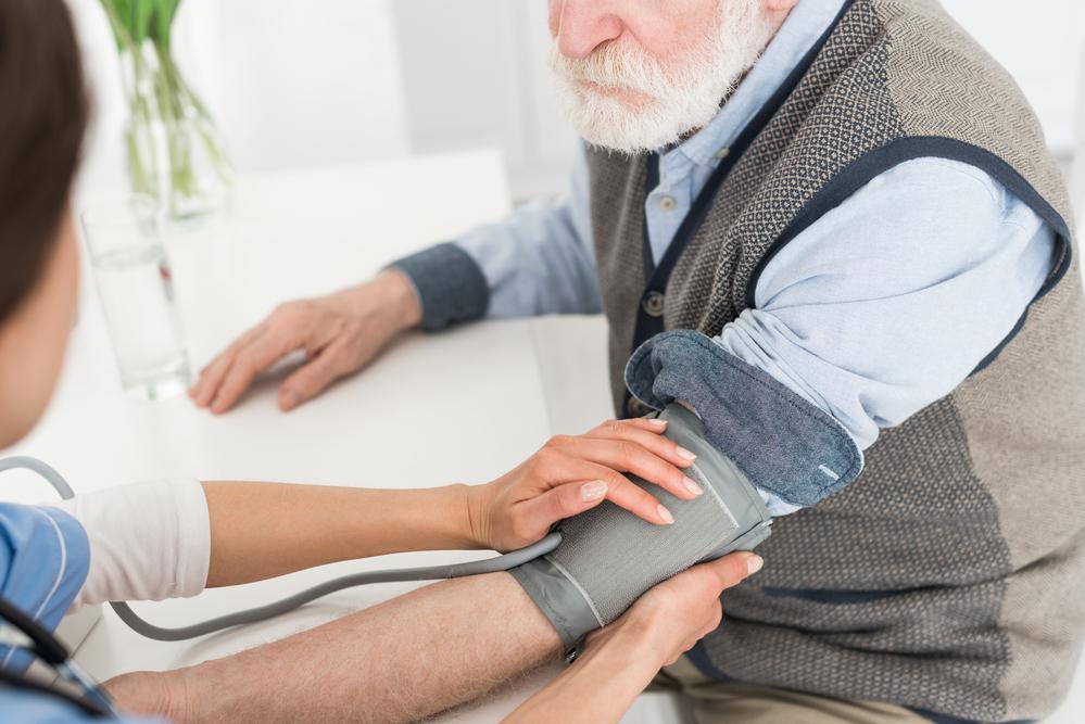 Nurse helping elderly man take blood pressure at home