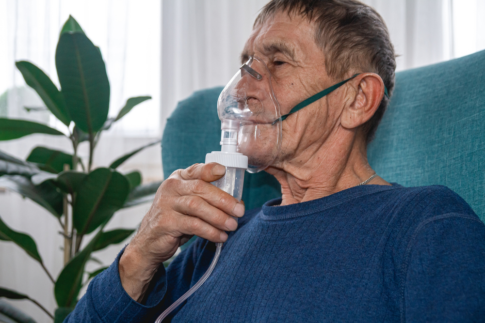 Elderly man in armchair with oxygen mask on
