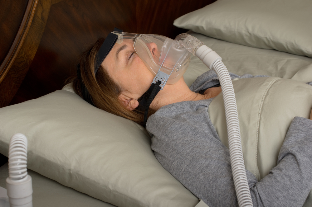 Woman sleeping with CPAP machine on